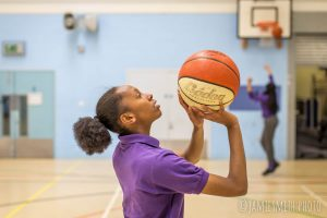 Photo of school girl playing basketball