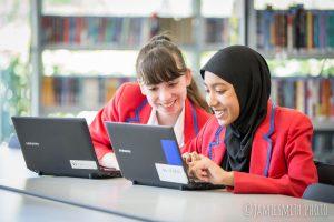 Photo of school girls using laptops